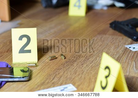 Id tents at crime scene after gunfight indoors. Gun cartridges as evidence on crime scene investigation process stock photo
