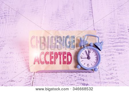 Word writing text Challenge Accepted. Business concept for to participate or undertake in a competitive situation Mini blue alarm clock stand tilted above buffer wire in front of notepaper. stock photo