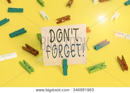 Text sign showing Don T Forget. Conceptual photo used to remind someone about important fact or detail Colored clothespin papers empty reminder yellow floor background office. stock photo