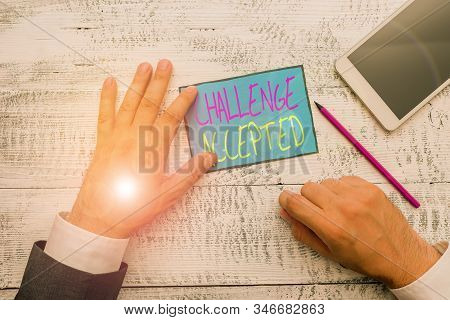 Word writing text Challenge Accepted. Business concept for to participate or undertake in a competitive situation Hand hold note paper near writing equipment and modern smartphone device. stock photo