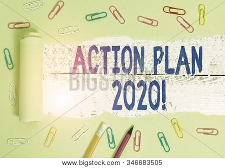 Handwriting text writing Action Plan 2020. Concept meaning proposed strategy or course of actions for current year Stationary and torn cardboard placed above a wooden classic table backdrop. stock photo