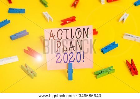 Text sign showing Action Plan 2020. Conceptual photo proposed strategy or course of actions for current year Colored clothespin papers empty reminder yellow floor background office. stock photo