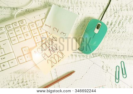 Writing note showing Action Plan 2020. Business photo showcasing proposed strategy or course of actions for current year Writing equipments and computer stuff placed on wooden table. stock photo