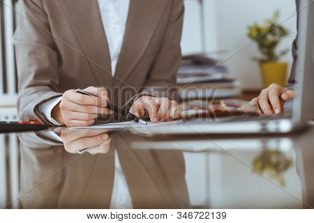Two female accountants checking financial statement or counting by calculator income for tax form, hands close-up. Internal Revenue Service inspector checking financial document. Planning budget and audit concept stock photo