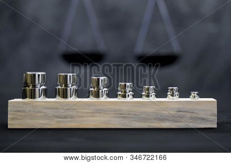 Shiny metal weight weights of various weights on the background of scales. Concept of weighing accuracy. Black and white image. stock photo