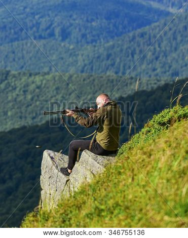 Hunter hold rifle. Hunter spend leisure hunting. Hunting in mountains. Man brutal gamekeeper nature landscape background. Hunting masculine hobby concept. Regulation of hunting. Focused on target stock photo