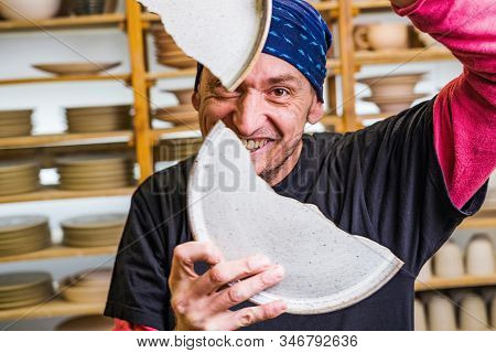 Funny potter smiling through the broken ceramic hand made plates in his studio ih front of pottery art products, small art business concept stock photo