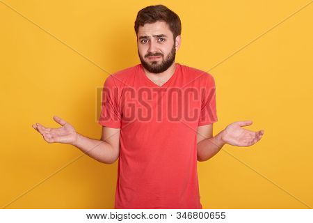 Close up portrait of young man posing isolated over yellow background, being at loss, showing helpless gesture with arm and hands, attractive girl wearing red casual t shirt. Body language concept. stock photo