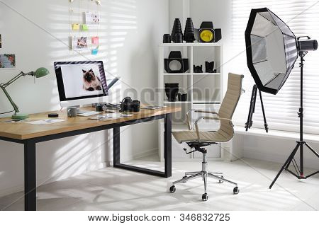 Photographer's workplace with professional camera and computer in office stock photo