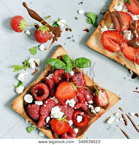 Toast with strawberries, raspberries, cherries, mint and cottage cheese for breakfast. Healthy breakfast, Ruddy bread toast. Traditional American and European summer breakfast: sandwiches of toast stock photo