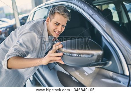 Man preparing to buy an automobile in showroom. Business concept.  Stylish man checking an auto before driving. stock photo