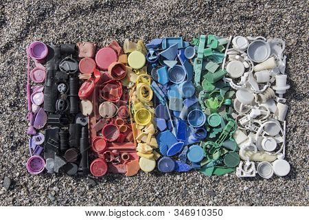 gradient color of plastic parts, degraded still life of plastic caps and different plastic pieces found on the beach, aerial view of the still life of plastic pieces found on the beach stock photo