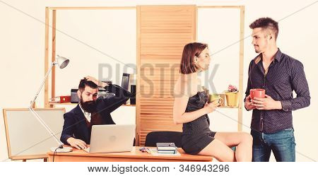 Having rest for good work. Pretty woman and handsome man having rest in office while colleague working in background. Managers drinking tea in rest hour. Young coworkers enjoying rest break at work stock photo