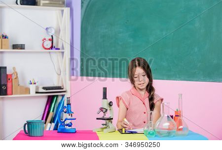 Biology education. Science lesson. School laboratory. Small girl with microscope. Girl biology class testing tubes. Scientific experiment. Fascinating lesson. Explore microbiology. Study biology stock photo