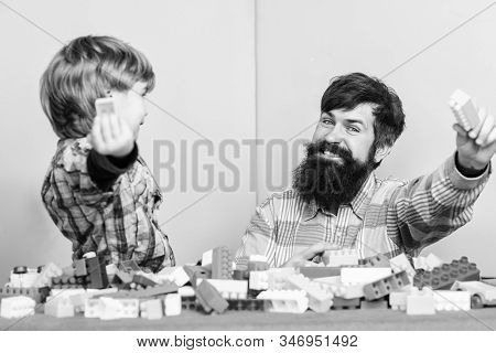 Every dad and son must do together. Dad and kid build plastic blocks. Child care development. Family leisure. Father son game. Father and son create constructions. Bearded man and son play together stock photo