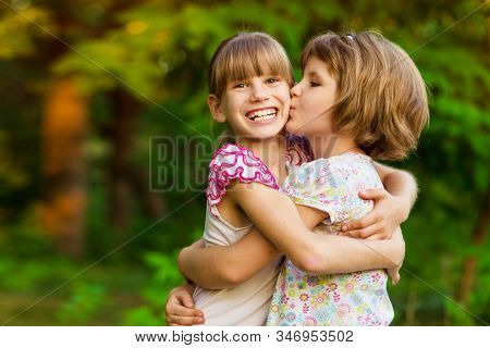 Little girl is very happy that she has sister. Loving sister hugging cute little girl showing love care support. Sincere warm relationships. Concept of happy family, adoption stock photo