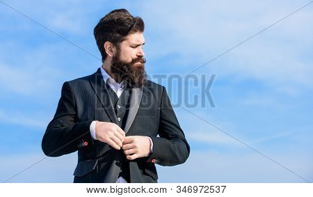Fashion trend. Guy beard and mustache wear formal clothes. Just right. Businessman bearded face sky background. Flawless outfit. Man formal suit adjusting jacket. Male fashion formal menswear stock photo