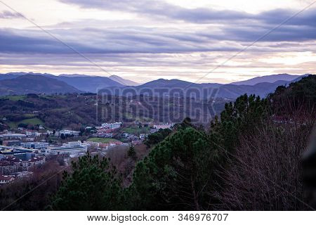 top aerial view of the inside area of donostia san sebastian spain with mountains and forest under cloudy sky in winter stock photo