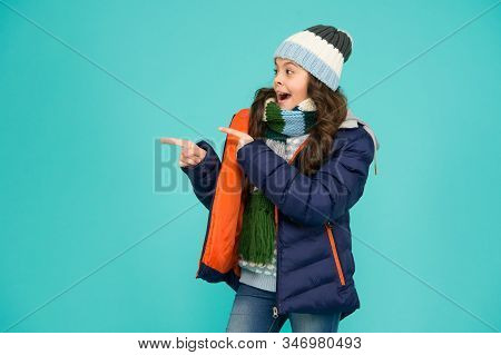 Dont just walk past. Happy girl pointing at something. Little child presenting product. Product promotion. Promoting and marketing. Product sale. Winter sale. Product advertising, copy space. stock photo