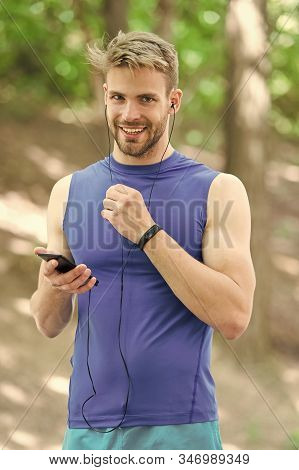 Set up application. Sportsman with smartphone and smart watch prepare for jog. Training with sport application is more fun. Set up route for run using application. Man smartphone ready to start jog. stock photo