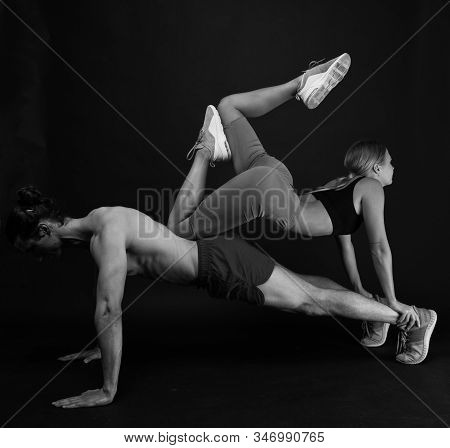 Sporty family. Couple workout. Exercises for muscles. Personal instructor in gym. Clothes for workout training. Feeling support. Sportsman push ups workout with fit girl on back. Couple loving sport. stock photo