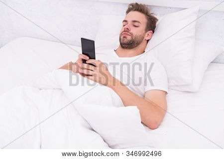 morning vibes. whole world in phone. he is blogging. flirting and sending text message. internet addiction and mobile abuse concept. man in bed chatting. man use smartphone from the early morning. stock photo