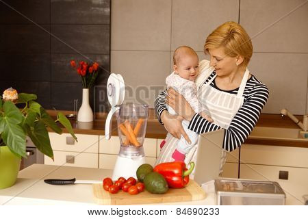Young mother holding baby in arms, preparing baby food in the kitchen. stock photo