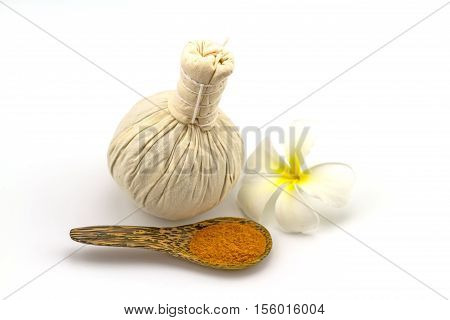 Spa herbal compressing ball white frangipani flowers (Plumeria spp Apocynaceae Pagoda tree Temple tree) and turmeric powder in wooden spoon on white background stock photo