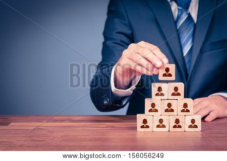 Human resources corporate hierarchy concept and multilevel marketing - recruiter complete team represented by wooden cube by one leader person (CEO) and icon. stock photo
