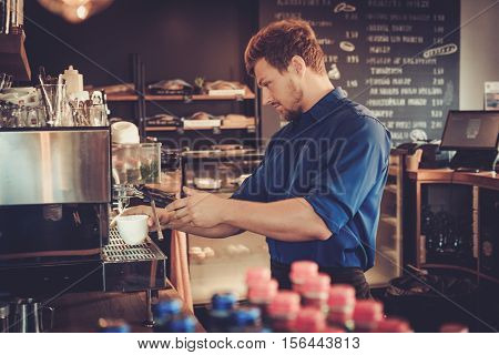 Handsome barista preparing cup of coffee for customer in coffee shop stock photo