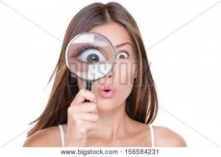 Funny expression. Shocked woman looking through a magnifying glass. Surprised Asian girl looking ast