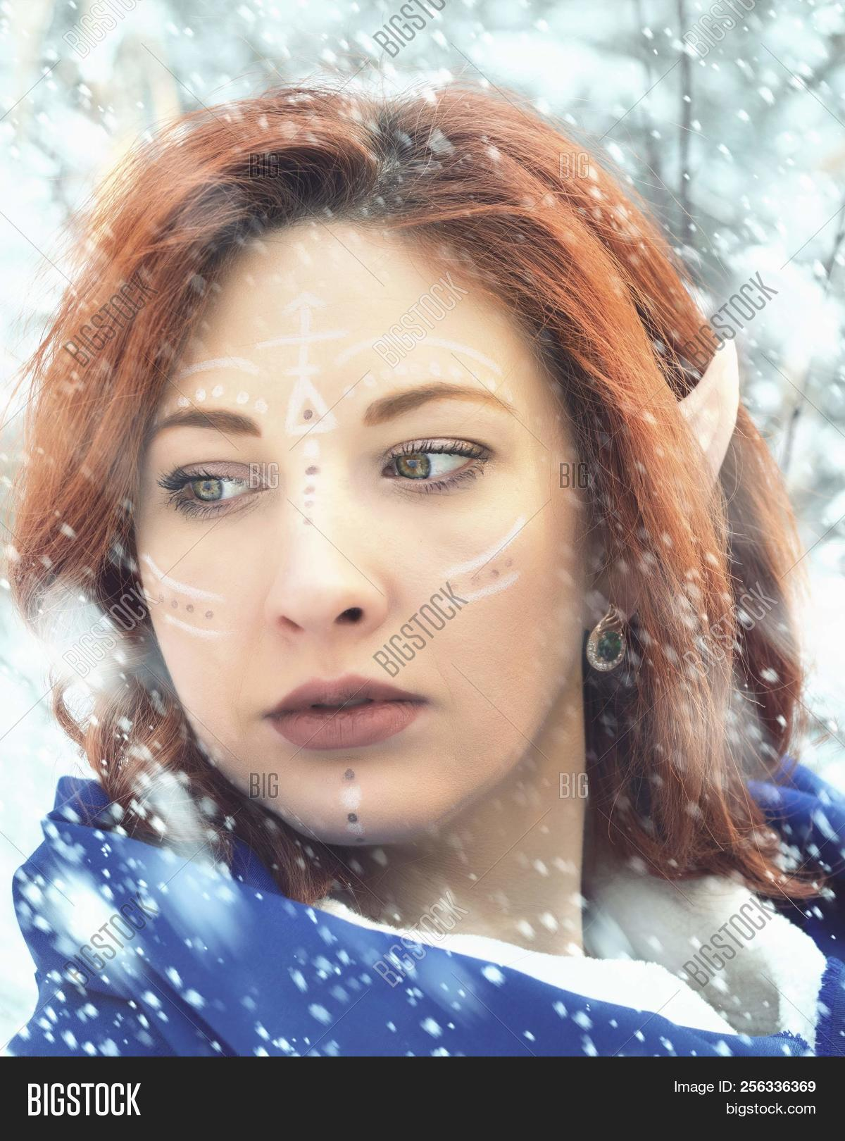 Elf Fairy woman. Close up portrait of an elf girl. Cold snowstorm in winter.