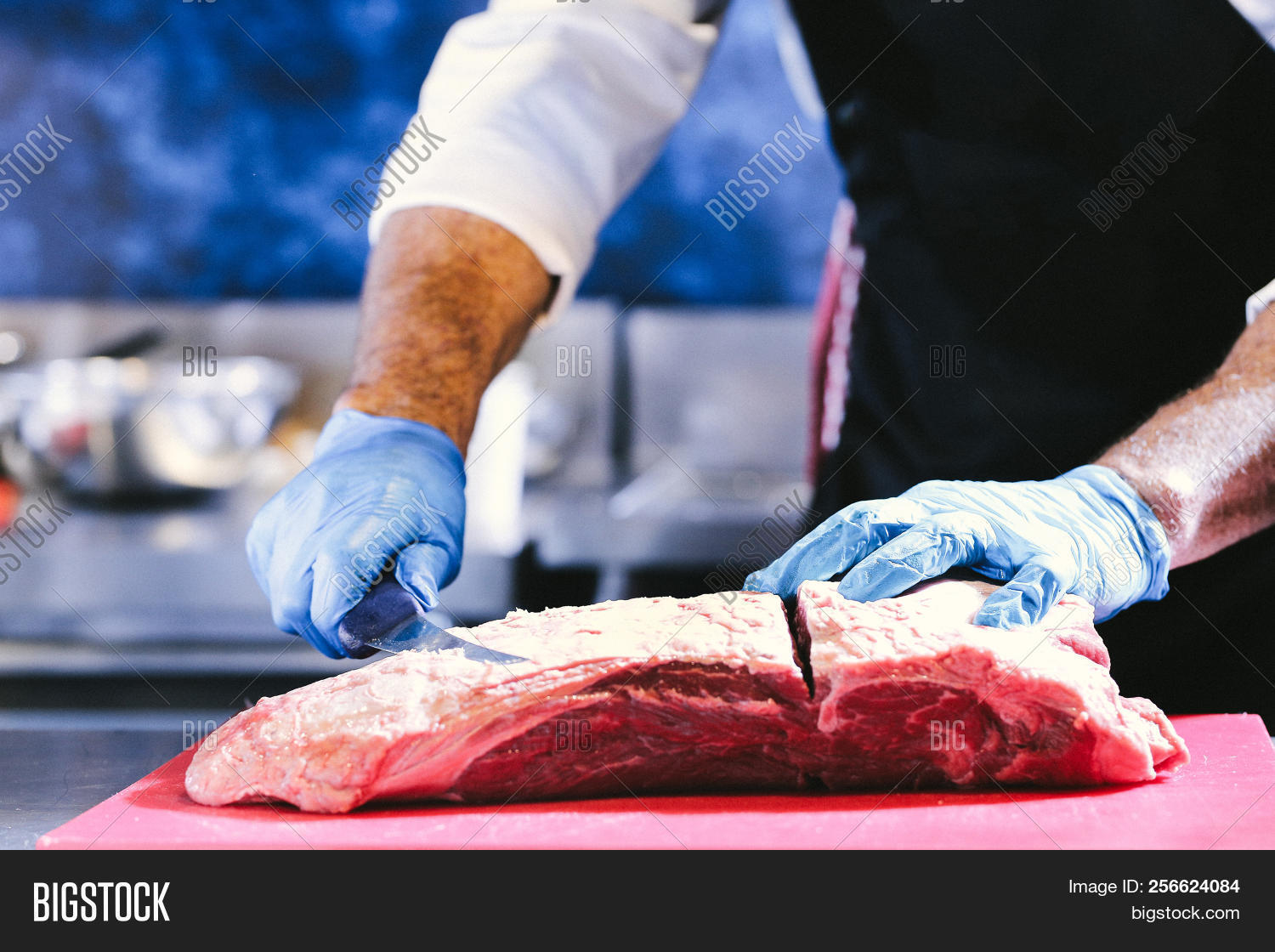 Butcher cutting pork meat on kitchen, Chef cutting fresh raw meat on board, Close up of butcher cutt