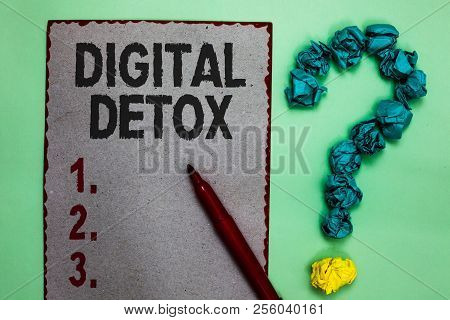 Handwriting text writing Digital Detox. Concept meaning Free of Electronic Devices Disconnect to Reconnect Unplugged Gray paper marker crumpled papers forming question mark green background. stock photo