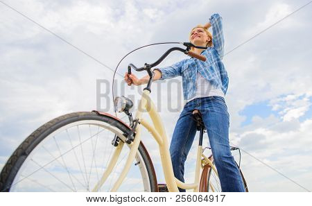 Enjoy cycling cruiser bike. Woman feels free while enjoy cycling. Most satisfying form of self transportation. Cycling gives you feeling of freedom and independence. Girl rides bicycle sky background. stock photo