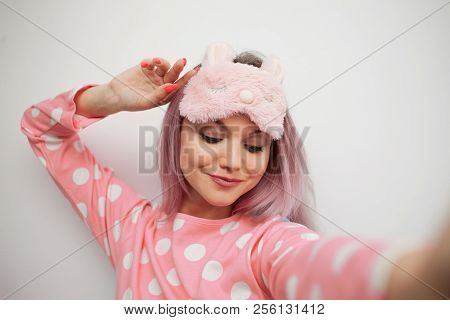 Selfie portrait of charming girl in pajamas and sleep mask. Woke up in the morning, charge of vivacity stock photo
