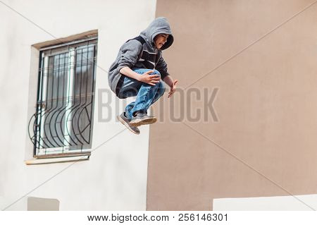 Teenage Boy In The Hood On A Street In A Big City Next To A High-rise Building Alone. Concept Of A T