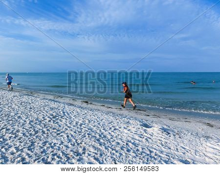 The people running at beach walking on Siesta key beach with white sand. stock photo