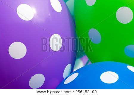Background of blue, green and purple balloons with the white circles on them. The optimistic picture, the symbol of happiness and joy stock photo
