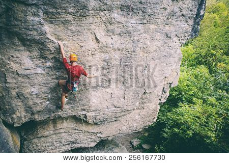A man in helmet climbs the rock. Climbing in nature. Fitness outdoors. Active lifestyle. Extreme sports. The athlete trains on a natural relief. Rock climbing in Ukraine. stock photo
