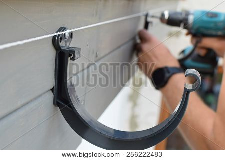 Man hands installing dark grey plastic roof gutter holder on wooden eaves screwing screws with screwdriver for drainage system of roof. stock photo