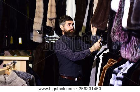 Macho with furry coats on background. Luxury shopping concept. Man with beard and mustache looking for fur coat. Guy with surprised face looks at fur coat price. stock photo