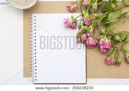 Mockup with blank notepad, cup of coffee and little garden pink roses. Morning still life. stock photo
