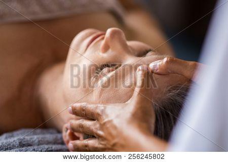 Closeup face of mature woman having facial massage at spa. Senior woman lying at spa while a massage