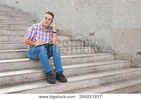 Pensive male entrepreneur listening to colleague on phone and looking into distance. Serios purposeful freelancer sitting on stairs and making remarks in diary. Man at work concept stock photo