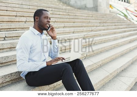 Happy black businessman working on laptop. African-american insuranse agent checking email on computer, talking on mobile, sitting on the stairs outdoors in urban area stock photo