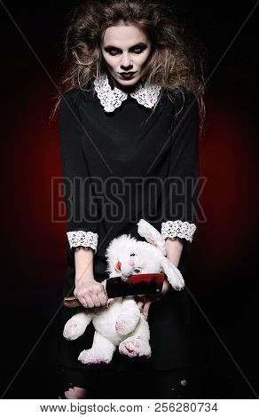 Horror shot: a scary wicked girl with rabbit toy and bloody knife in hands stock photo