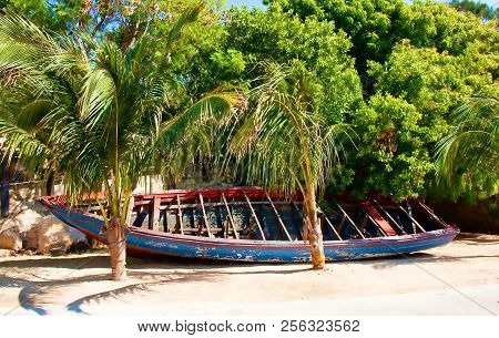 An old wooden rowboat under palm trees on a tropical beach stock photo