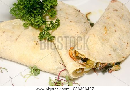 Typical mexican food made with a folded tortilla and filled with pumpkin leaf stock photo