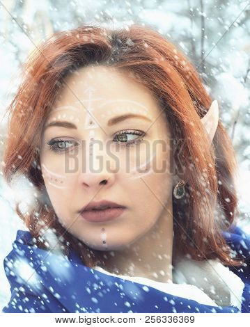 Elf Fairy woman. Close up portrait of an elf girl. Cold snowstorm in winter. stock photo